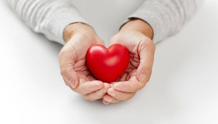 close up of senior man holding red heart in hands