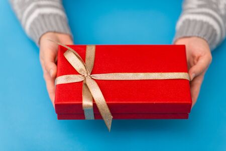 hands holding red christmas gift box