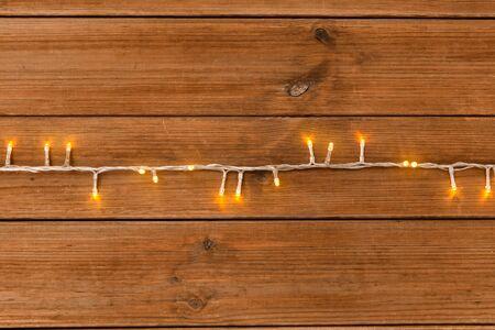 christmas garland lights on wooden background Banco de Imagens