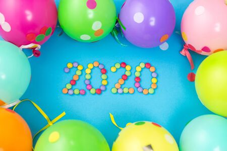 holidays, celebration and decoration concept - 2020 new year party date with colorful balloons on blue background Imagens