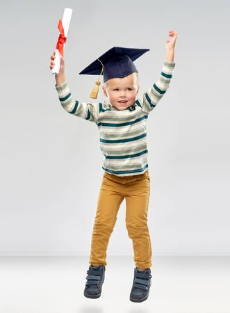 elementary school, preschool education and success concept - portrait of smiling little boy in mortar board with diploma celebrating triumph over grey background