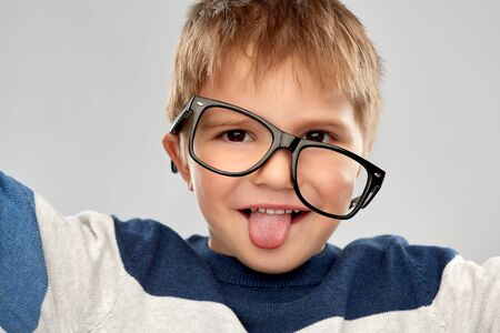 school, education and vision concept - portrait of smiling little boy with crookedly worn glasses showing tongue over grey background