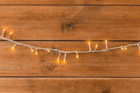 christmas, holidays and illumination concept - electric garland lights on wooden background Banco de Imagens