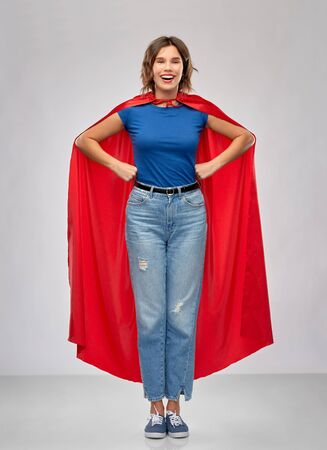 El poder de la mujer y el concepto de la gente - mujer feliz en capa roja de superhéroe sobre fondo gris