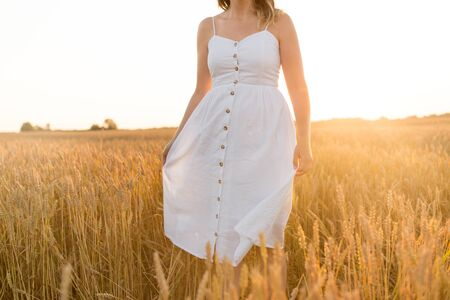 harvesting, nature, agriculture and prosperity concept - young woman in white dress walking through ripe wheat spickelets on cereal field