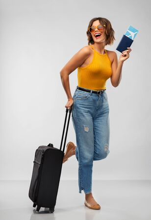travel, tourism and vacation concept - happy laughing young woman in mustard yellow top with air ticket, passport and carry-on bag over grey background