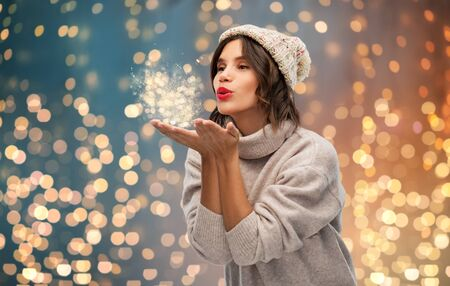 christmas, season and people concept - happy young woman in knitted winter hat and sweater sending air kiss over festive lights background Stock fotó