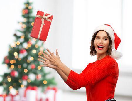 groeten en wintervakantie concept - gelukkig lachende jonge vrouw in santa helper hoed vangen rode geschenkdoos over kerstboom lichten achtergrond Stockfoto