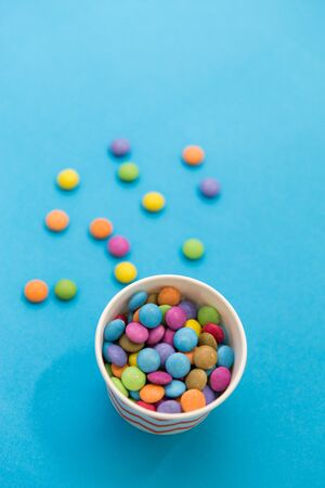 food, confectionery and sweets concept - candy drops in paper cup on blue background Фото со стока