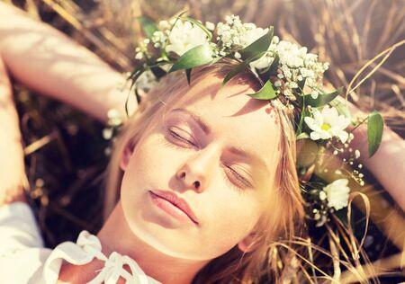natura, vacanze estive, vacanze e concetto di persone - donna sorridente felice in ghirlanda di fiori sdraiata sulla paglia