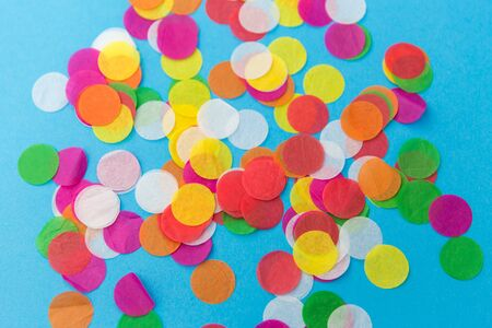 party, celebration and decoration concept - colorful confetti on blue background