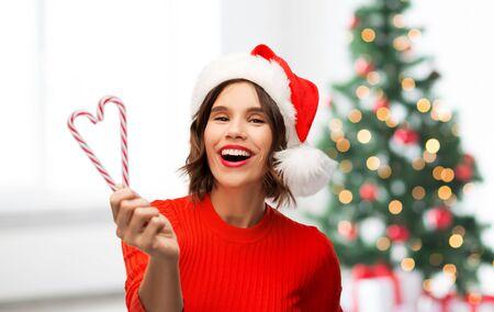 wintervakantie en mensen concept - gelukkig lachende jonge vrouw in santa helper hoed met zuurstokken over kerstboom lichten achtergrond