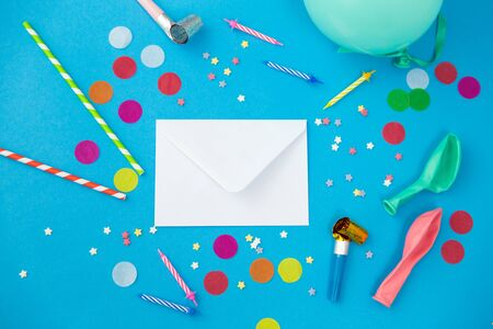 celebration and decoration concept - white postal envelope birthday party props and colorful confetti on blue background