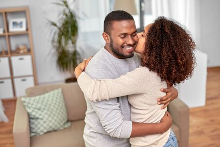 Happy african american couple kissing at home Reklamní fotografie - 133342126