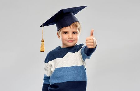 Happy little boy in mortarboard showing thumbs up