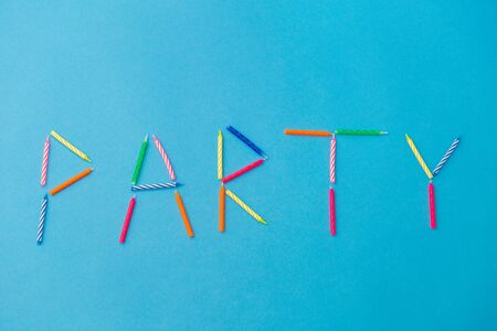 Word party made of birthday candles on blue Banco de Imagens