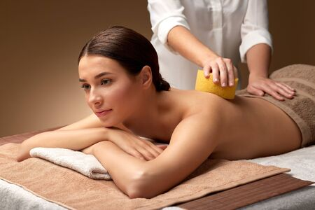 woman having back massage with sponge at spa Stock Photo