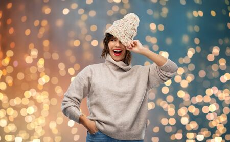 Happy young woman in knitted winter hat and sweater
