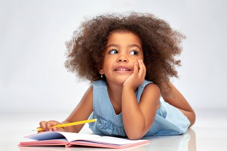 Happy little african american girl with sketchbook