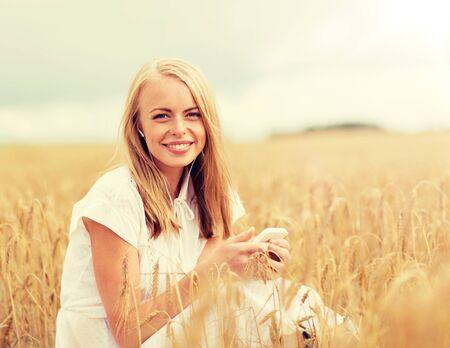 Concepto de vacaciones, vacaciones, tecnología y personas de verano - mujer joven sonriente con vestido blanco con teléfono inteligente y auriculares escuchando música en el campo de cereales