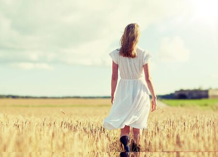 happiness, nature, summer holidays, vacation and people concept - young woman in white dress walking along cereal field Imagens