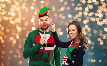 christmas, photo booth and holidays concept - happy couple in ugly sweaters posing with party props over festive lights background Zdjęcie Seryjne