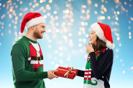 people and holidays concept - happy couple in santa hats with christmas gift at ugly sweater party over festive lights on blue background