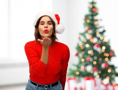 winter holidays and people concept - happy young woman in santa helper hat sending air kiss over christmas tree lights background