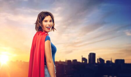 womens power and people concept - happy woman in red superhero cape over sunset in tallinn city background