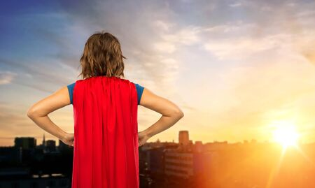 womens power and people concept - back view of young woman in red superhero cape over sunset in tallinn city background