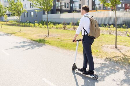 businessman with backpack riding electric scooter Stock Photo