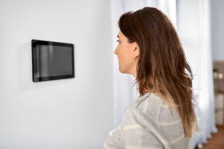 woman looking at tablet computer at smart home