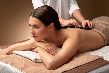 beautiful woman having hot stone massage at spa