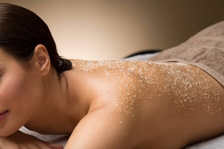 close up of woman with sea salt on skin at spa