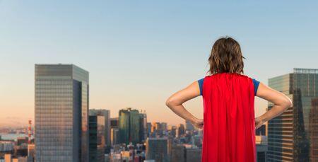 woman in red superhero cape over tokyo city 写真素材