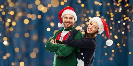 christmas, people and holidays concept - portrait of happy couple in santa hats at ugly sweater party over festive lights on dark night background Zdjęcie Seryjne