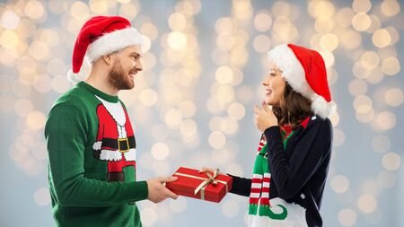 people and holidays concept - happy couple in santa hats with christmas gift at ugly sweater party over festive lights background Stock Photo