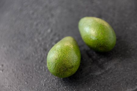 food, eating and vegetable concept - close up of two avocados on wet slate stone background