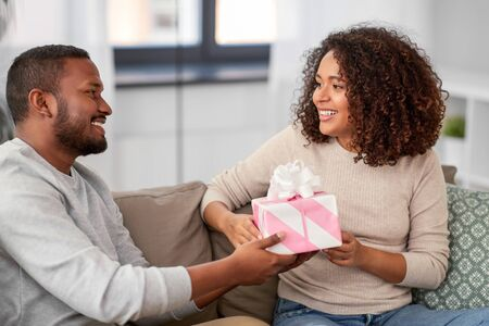 holiday, greeting and people concept - happy african american couple with gift at home