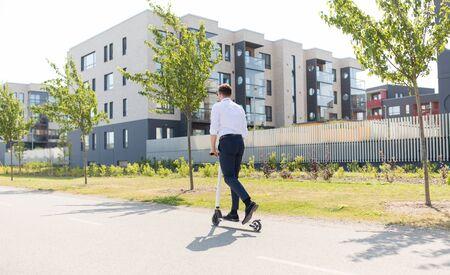 affari e persone e concetto - giovane uomo d'affari in sella a uno scooter elettrico all'aperto Archivio Fotografico