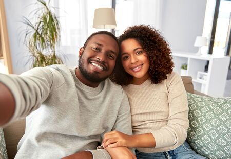 family, technology and people concept - happy african american couple taking selfie at home Foto de archivo