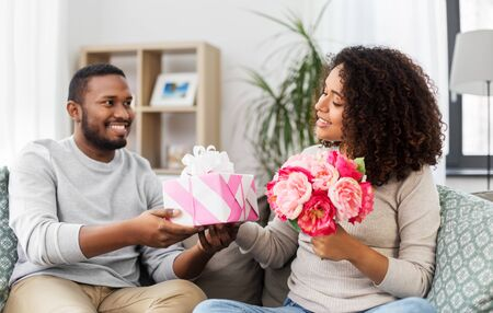 holiday, greeting and people concept - happy african american couple with bunch of flowers and gift at home Фото со стока