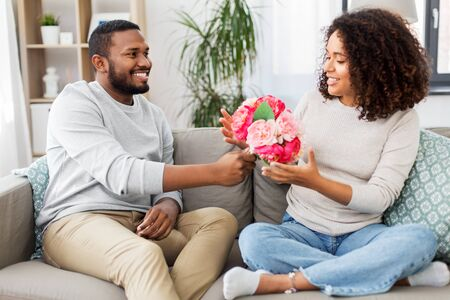 holiday, greeting and people concept - happy african american couple with bunch of flowers at home