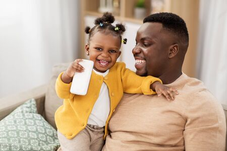 family, fatherhood and technology concept - african american father and little baby daughter with smartphone at home