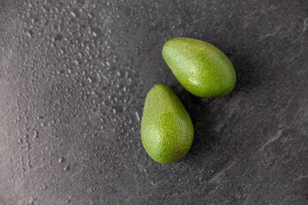 two avocados on wet slate stone background Banco de Imagens