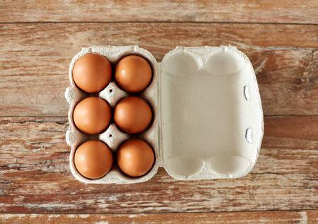 Cerca de huevos en caja de cartón sobre mesa de madera