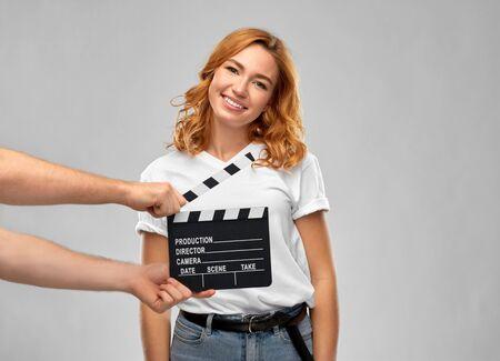 concept de production, de réalisation de films et de divertissement - femme ou actrice heureuse au casting en studio et mains avec clap sur fond gris