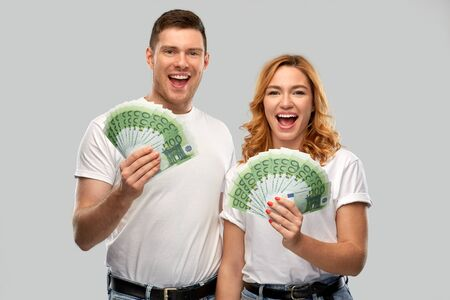 finance, saving and people concept - portrait of happy couple in white t-shirts with euro money over grey background Stock fotó