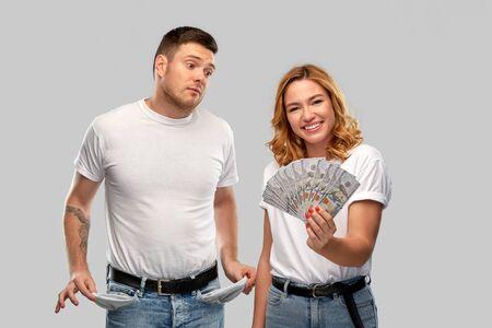 Finanz-, Spar- und Paarkonzept - glückliche junge Frau im weißen T-Shirt mit Dollargeld und trauriger Mann mit leeren Taschen auf grauem Hintergrund