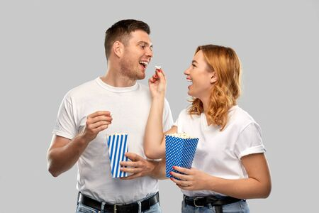 food, entertainment and people concept - portrait of happy couple in white t-shirts eating popcorn over grey background Banco de Imagens